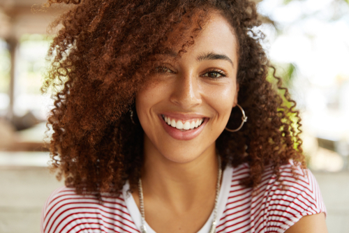 A young woman with a beautiful smile and curly hair