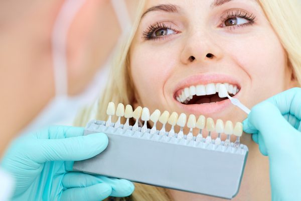 dentist applying teeth whitening treatment to woman patient